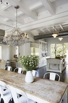 Just the right mix of rustic with industrial and vintage elements, and the touch of glamour in the chandelier in this kitchen from Veranda magazine