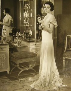 Claudette Colbert contemplating in front of a beautiful vanity table, 1930's.
