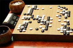 Go: A strategic board game involving tactics, observation and cunning. Originating in China and having been played for at least the past 2000 years, it's famous for providing an ample strategic challenge despite having relatively simple rules. A 2-player game, it's played on a 19×19 grid and uses black and white stones with which a player must attempt to control a larger part of the board by taking it in turns to place a stone in a vacant grid space.