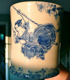 A large chunky mug, thrown in cream earthenware. Each piece is individually hand painted and decorated with a blue 'Delft' happy girl swinging in the trees. No transfers or decals are used in the production of this mug. Each piece is different and unique. Girl Swinging, In The Tree, Delft, Happy Girls, Earthenware, Pillar Candles, Drawer, Decals, Plush