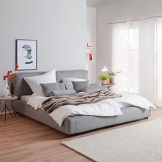 graue Wand - graues Bett - beige-grauer Teppich