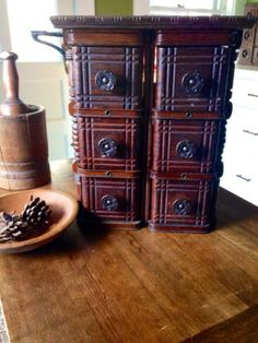 Up-Cycled Apothecary Chest made from old Singer Sewing Machine Drawers with the metal brace repurposed as a towel bar!