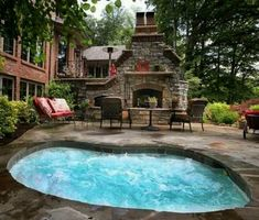 Stone patio with large hot tub & massive outdoor fireplace-oh my! I love the feel of this outdoor area!