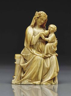 A CARVED IVORY GROUP DEPICTING THE VIRGIN AND CHILD, FRENCH, SECOND HALF 14TH CENTURY