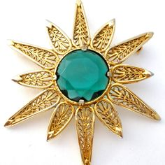 Vintage Jewelry Brooches - This is a gold tone starburst or star pin with an open work design and round emerald green rhinestone. It can be worn as a pendant or as a brooch, has an open work design an