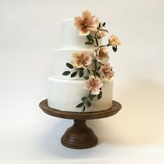 Ivory wedding cake with blush wild roses made from sugar.