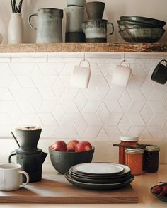 Cain's stoneware, shown here, consists of necessary tools for their daily routine, including coffee-brewing. The countertops are quartz composite from a local company. Cain learned how to fire the ceramic tiles herself to form the geometric backsplash. Kitchen Ikea, White Kitchen Backsplash, New Kitchen, Kitchen Decor, Backsplash Ideas, Kitchen White, Ceramic Tile Backsplash, Copper Backsplash, Beadboard Backsplash