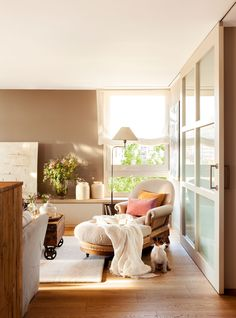 Salón con paredes en beige, suelo de madera, chaise longue y puerta corredera