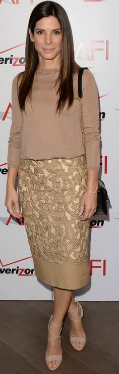 Sandra Bullock: Sweater and skirt – Burberry  Shoes – Brian Atwood  Bracelet – EF Collection