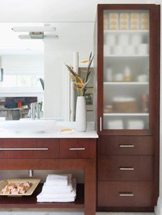 This coordinating cabinetry brings a crisp, modern look to this bathroom without sacrificing storage. The open vanity keeps the grooming space open and bright, while a tall shelving unit adds height and plenty of storage space for toiletries and linens.