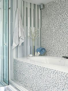 Seamless Style | Adding to the room's luxurious amenities is a large soaking tub. Clad in the same mosaic tile as the rest of the room, the tub blends into the room for seamless style. Heated floors keep this entirely-tiled bathroom cozy and not cold.