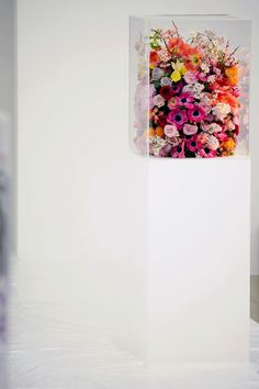 Glass box of colorful flowers on a pedestal