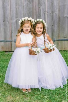 Flower girls donning white rose headbands carry wicker baskets of petals at a rustic chic wedding ceremony at the Historic Barns of Nipmoose.