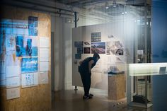 Great by Design: British Architecture, Asian Vision. Installation shot. A visitor checks out the detail in Zaha Hadid Architects development drawings. Photography by Virgile S Bertrand