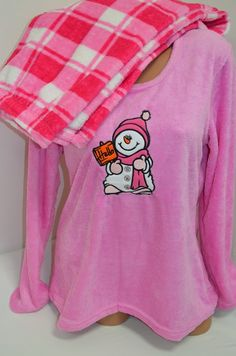 Много мека, топла и ефектна пухкава пижама в свежи цветове. Горната част е с дълги ръкави в розово и апликация - снежен човек отпред. Долното е дълъг панталон в свежо каре. С тази пижама ще ви бъде топло и приятно през студените зимни нощи.