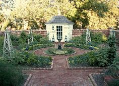 Potager garden? Like the brick wall, obelisks and little shed