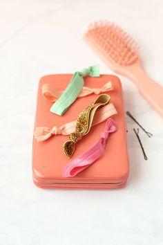 DIY Hair Ties ~  5/8″ foldover elastic (1 yd = 4 ties) Scissors Measuring tape/ruler  Step 1: Measure and cut a 9″ strip of elastic. Step 2: Fold the strip of elastic in half. Step 3: Tie the ends in a knot. Step 4: Repeat.