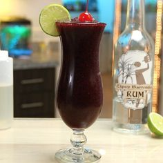 If you want to fall in love with a slushy rum cocktail, you need to check out this Frozen Blueberry Daiquiri. This gorgeous frozen rum cocktail mixes light rum, lime juice, simple syrup, and frozen blueberries, and is garnished with a cherry and lime wheel to up those tropical mixed drink vibes. Fun Drinks, Yummy Drinks, Beverages, Tropical Mixed Drinks, Blueberry Cocktail, Beach Cocktails, Cocktail Mix, Tipsy Bartender