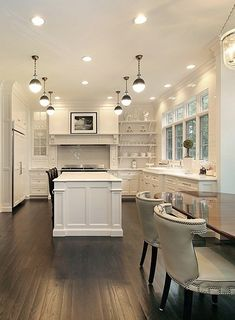 dark wood floor kitchen. Open plan kitchen and dining room with dark wood floors  traditional cabinetry upholstered chairs nailhead detailing Molding on the end of Love contrast white By Simmons Estate
