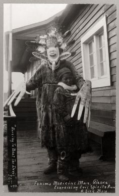 """""""Working to beat the devil - Eskimo medicine man exorcising evil spirits from a sick boy"""", 1900."""