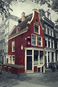 Amsterdam - the Netherlands Een prachtig Rijksmonument aan de Reguliersgracht, op de hoek met de Prinsengracht. Een karakteristiek rood gekleurd grachtenpand met klokgevel. Aan de zijkant een pothuis en aan de gevel een ooievaar (hier had in de 17e eeuw een vroedvrouw haar praktijk) en een zonnewijzer. Een plaatje.....