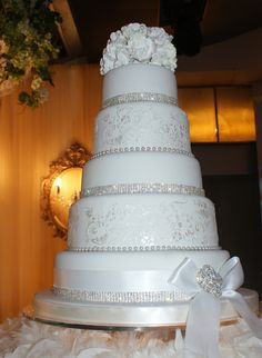 Lovelle - Glitz and Glitter. This gorgeous 5 tiered round cake is covered with white fondant and decorated with a crystal brooch. The alternate tiers includes a 6 row band of Swarovski Crystals. Glitter and glam wedding cakes are not only trendy but they'll be remembered and make for beautiful photos!