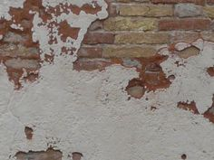 Worn brick wall partly covered in thin layer of concrete painted in cream color.
