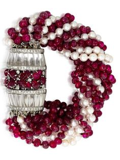 An Art Deco ruby, cultured pearl, diamond and rock crystal quartz bracelet, circa 1935. The nine-strand torsade bracelet composed of ruby and cultured pearl beads, completed by a dome of foliate design, enhanced with carved rubies, single-cut diamonds and rock crystal quartz; mounted in platinum. #ArtDeco #bracelet