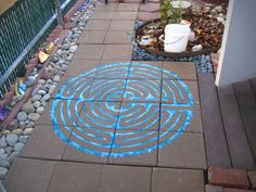 "Painted labrynth using Liquitex Glossies - worked beautifully on the porous pavers.  Each paver measures 11 5/8"" square - so the completed image is just shy of 4' x 4'  Obviously its too small to walk, but you can sit under the nearby tree and use a stick to ""walk"" the path."