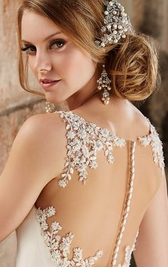 10,000 sparkling glass beads and Swarovski crystals elegantly adorn the illusion back detailing on this botanical-inspired sheath wedding dress from Martina Liana.