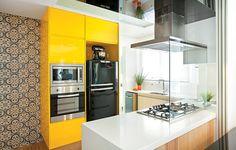 O armário de laca brilhante e amarela deu ar moderno à cozinha que é aberta para a sala. A cor divertida é equilibrada com o aço inox e o preto dos eletrodomésticos