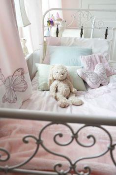 zachte pasteltinten in de meisjes slaapkamer met stalen bedframe