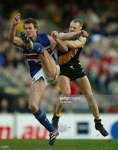 Luke Darcy #14 for the Bulldogs kicks away as Matthew Knights #33 for Richmond arrives to bump him, during the Round 10 Richmond Tigers v Western Bulldogs AFL match, played at the MCG, Melbourne, Australia on the 1st of June 2002.
