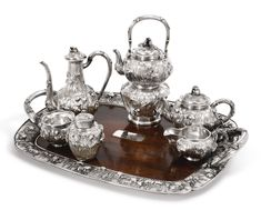 "A Japanese Export silver six-piece ""Iris"" tea set with matching silver-mounted wood tray, Arthur & Bond, Yokohama, circa 1900 boldly embossed with iris flowers on matted ground, comprising A Teapot, Coffee Pot, Kettle on Lampstand, Creamer, Sugar Bowl, Tea Caddy, and two-handled Tray with wood panel inlaid with silver iris border and mounted with a crested plaque marked on bases, lampstand apparently unmarked height of kettle on lampstand 13 in., length of tray over handles 26 1/2 in."