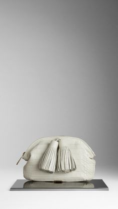 leather tassels | Alligator clutch bag with brogue-inspired oversize leather tassels