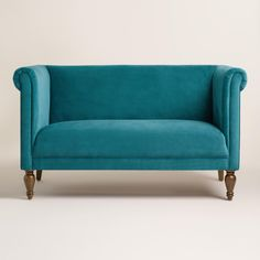 Boasting rolled shelter arms and sumptuous velvet upholstery in a pacific blue hue, our roomy loveseat is a fresh take on a cozy classic that's certain to brighten your seating arrangement.