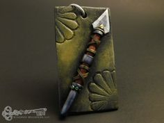 Spear: Forged from #polymerclay and mica powders my Armory Series grows. These #pendants are #handmade with simplicity and depth. Each piece of #jewelry in the armory are uniquely inspired by #fantasy, #history and #mythology. Armors, weapons, helms, and new creations will be crafted to fill the #armory!