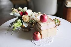 so in love with this centerpiece of deconstructed books, silver pitcher and apples