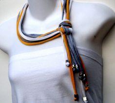 Ce collier noué comme un lasso est un ensemble de lanières en jersey de coton d'une longueur d'environ 75 cm (30 pouces) et terminées par des perles argentées. Le nouage se fait grâce à deux anneaux argentés.