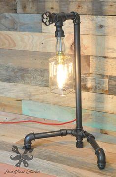 Lampe de table composée dun corp en acier de type Plumbing et dun abat-jour provennant dune bouteille de Whisky Jack Daniels découpée et polie.