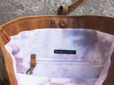 LARGE FOLD OVER LEATHER TOTE    + Beautiful, soft tan leather  + Hand dyed soft purple and pink tie dyed lining  + Inner zipper pocket and key hook  + Rivet details on bottom sides  + Magnetic clasp  + Leather strap/bow detail - removable  + Strap tied to bag and removable if you want to use as a clutch    MEASUREMENTS:  STRAP: 32  UNFOLDED: 14 x 15  FOLDED: 14 x 9    Scout & Catalogue is heavily influenced by the bohemian beach culture of Mexico. We strive to make pieces that remind...