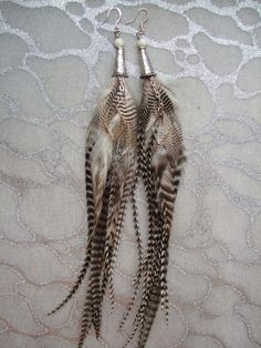 Earrings Feather Long Striped White Black - These feather earrings are very long and stylish. They showcase striped black and white feathers from Ducks, Pheasants, and Roosters. White shell beads top the silver metal cones which dangle silver chains with silver metal Diamond shaped charms and the long lushious feathers by MEDICINAdesigns, $69.99