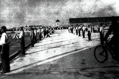 Punishment Standing at Dachau Concentration Camp. The long shadows could indicate that the punishment was administered late in the day, possibly after a long working day. 1941.