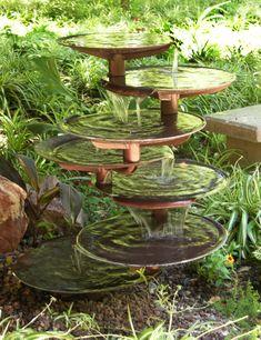 fontaine de jardin design avec coupes en cascade dans une verdure abondante