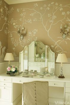 Suzanne Kasler - Beautiful bathroom with French sconces on de Gournay custom wallpaper framing Nancy Corzine folding vanity mirror flanked by crystal lamps with pleated lamp shades on white make-up vanity paired with Nancy Corzine vanity chair.