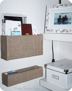 Cardboard boxes covered in burlap. Hang on wall. Cute, easy, space-saving organization!