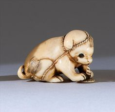 "IVORY NETSUKE Early 19th Century In the form of a puppy with inlaid eyes chewing on a sandal. Length 1.5"" (3.8 cm)."