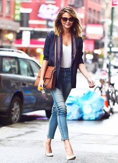 Chrissy Teigen pairs a structured blazer with casual finds like a t-shirt, blue jeans, and pumps