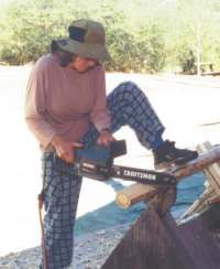 Dorothy uses her electric chainsaw to shave a tenon. Log Crib, Crib Spring, Electric Chainsaw, Homemade Quilts, Wood Ideas, House And Home Magazine, Masking Tape, Cribs