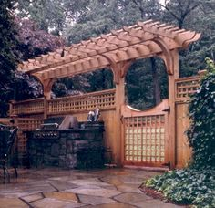 Fence with cantilevered arbor top and stone outdoor kitchen area